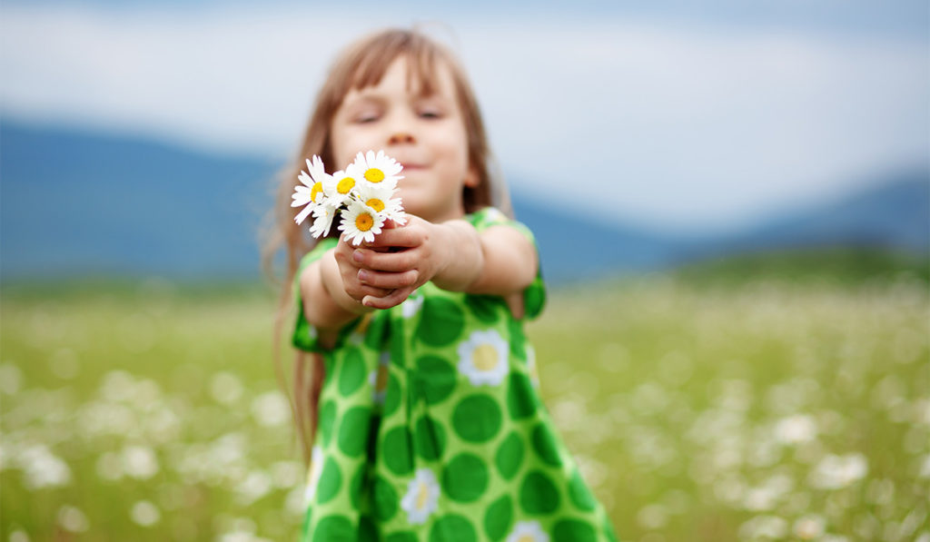Small child showing flowers